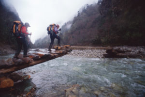 Bhutan, Rodophu Valley, female hikers crossing bridge